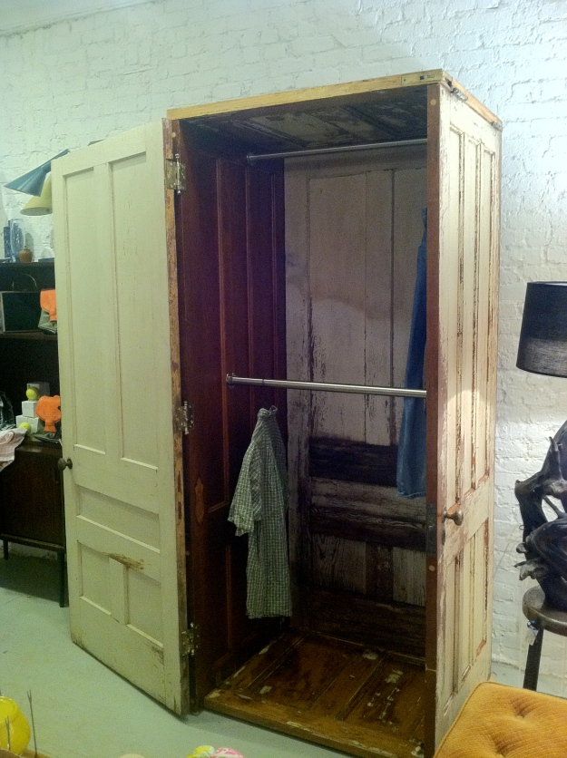 "Armoire with single door entry, made out of 5 vintage doors, 18 vintage hinges, and a double hanger that can accommodate long and short clothes. 83""h x 34""w x 30""deep."